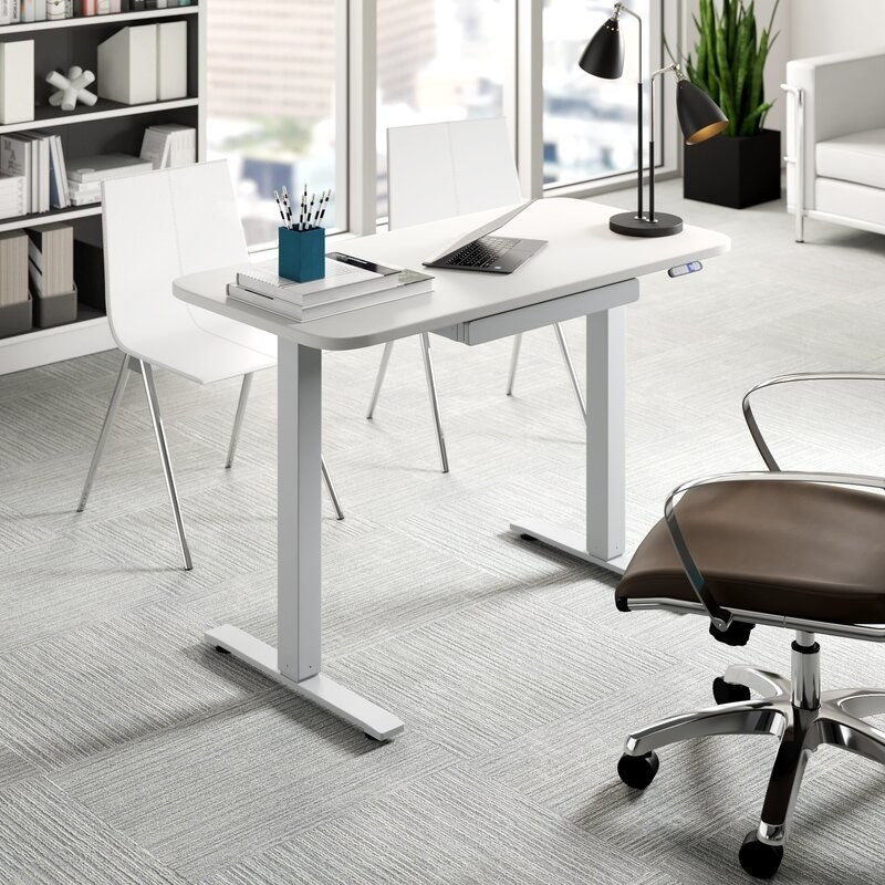 Adjustable standing desk in office space.