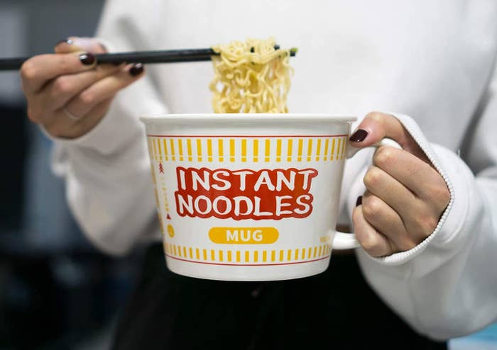 A person holding the noodle mug