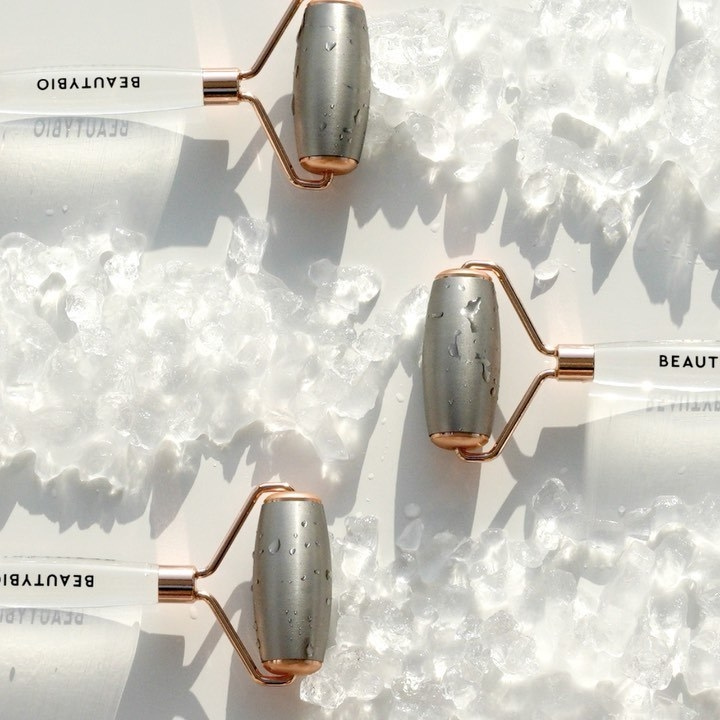 A trio of stainless steel rollers arranged around some crushed ice