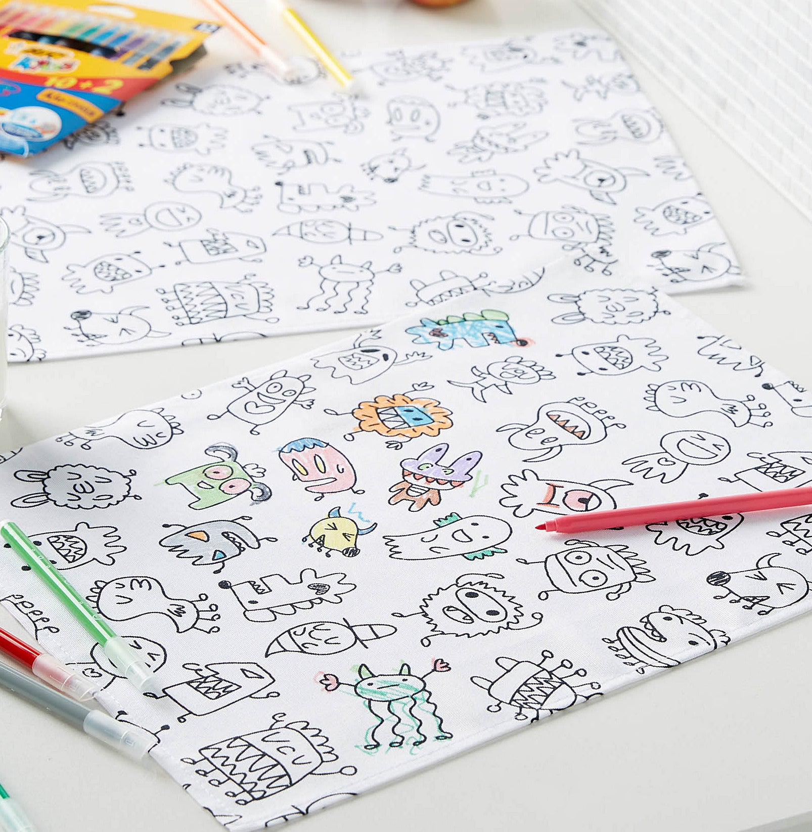 Two colour-in placemats with markers on top of them