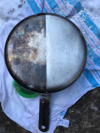 A reviewer's photo of a stainless steel pan that is tarnished on one side and clean on the other after being treated with the formula