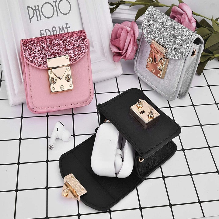 Three AirPods cases shaped like tiny crossbody bags in black, silver and pink