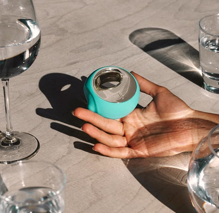 Hand holds blue Lelo Ora 3 oral sex simulator on a table of glasses
