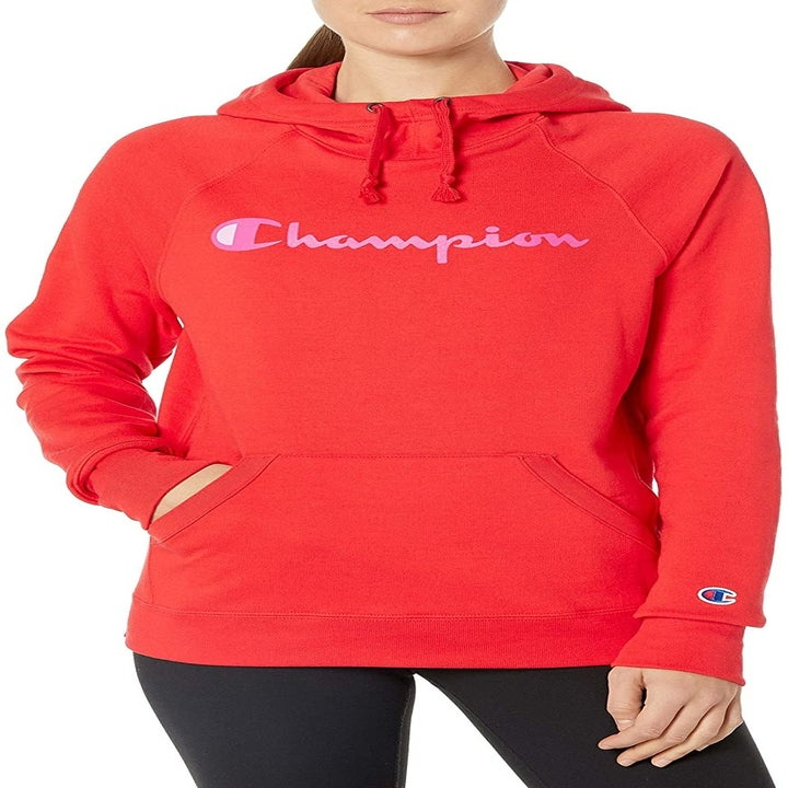 a model in a red pullover with the champion logo in pink