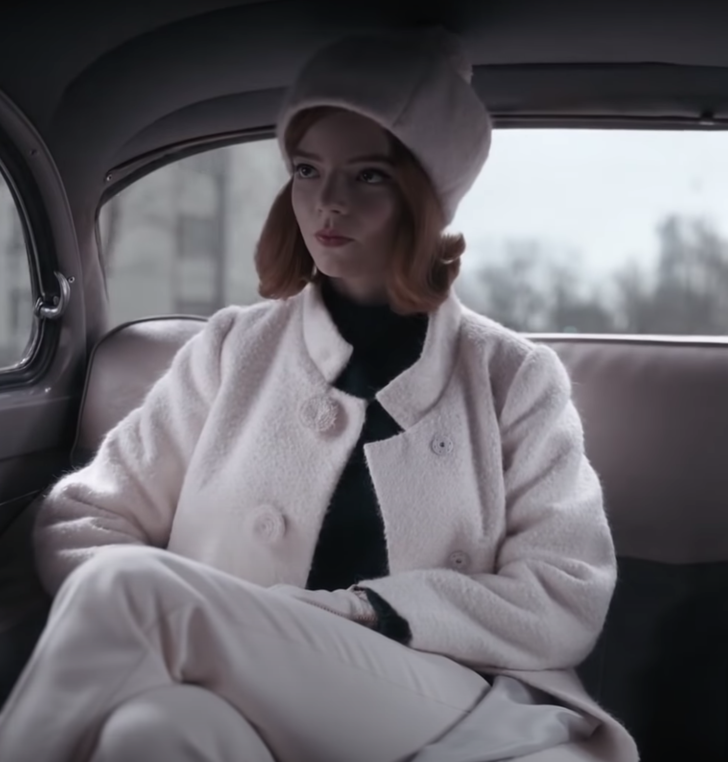 """Beth on """"The Queen's Gambit"""" wearing a white coat, pants, and hat"""