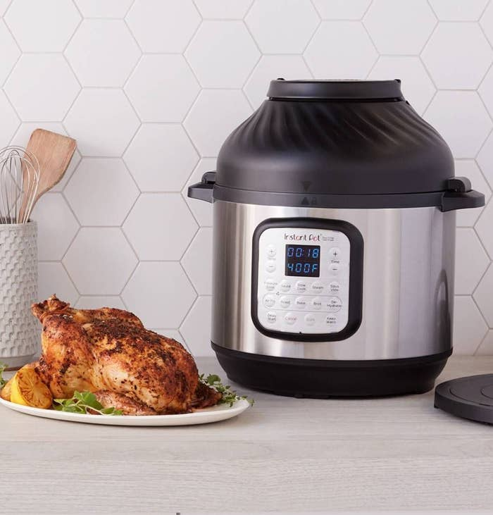 instant pot with an air fryer top next to a roast chicken on a counter