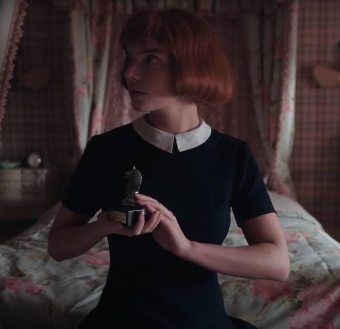 """Beth holding her trophy in """"The Queen's Gambit"""""""