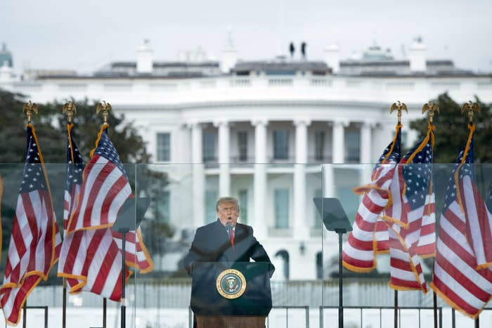 Trump speaks between three US flags on either side of him, standing behind a lectern and glass in front of the White House