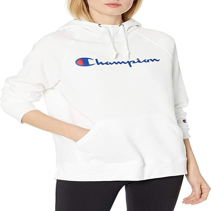 another model in the sweatshirt in white with the champion logo in blue