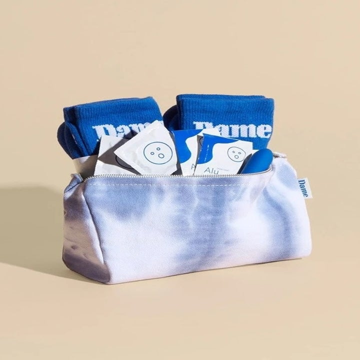 Dame Duo Kit with two pairs of blue socks, a two aloe-based lube packets, two latex condoms, and a blue and white tie-dye pouch