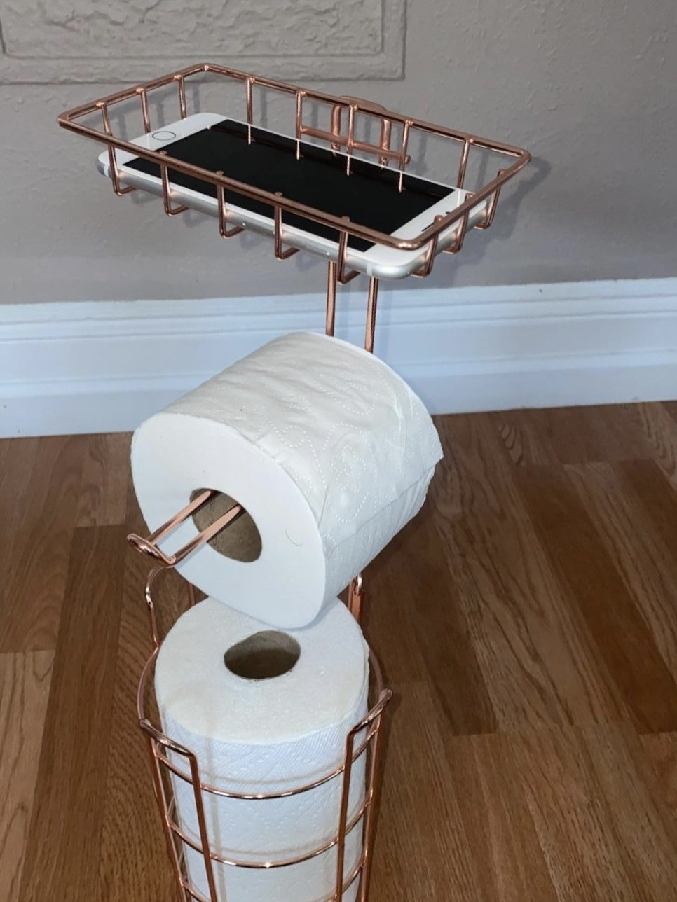 reviewer photo showing the toilet paper stand with their phone on top in the holder