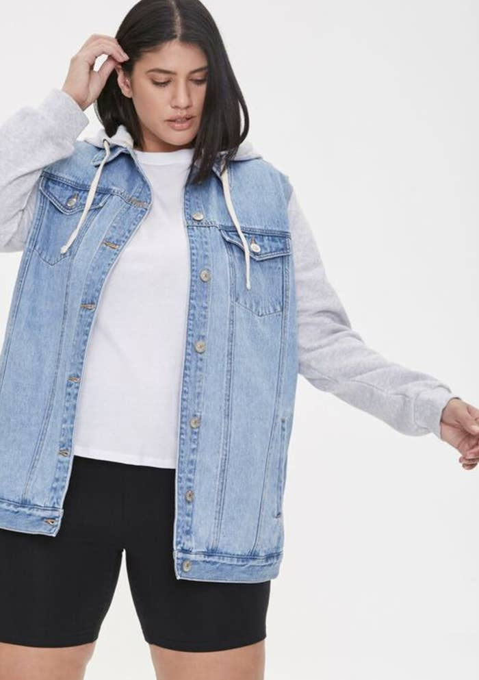 Model is wearing a denim jacket with grey cotton sleeves, a white top, and black biker shorts