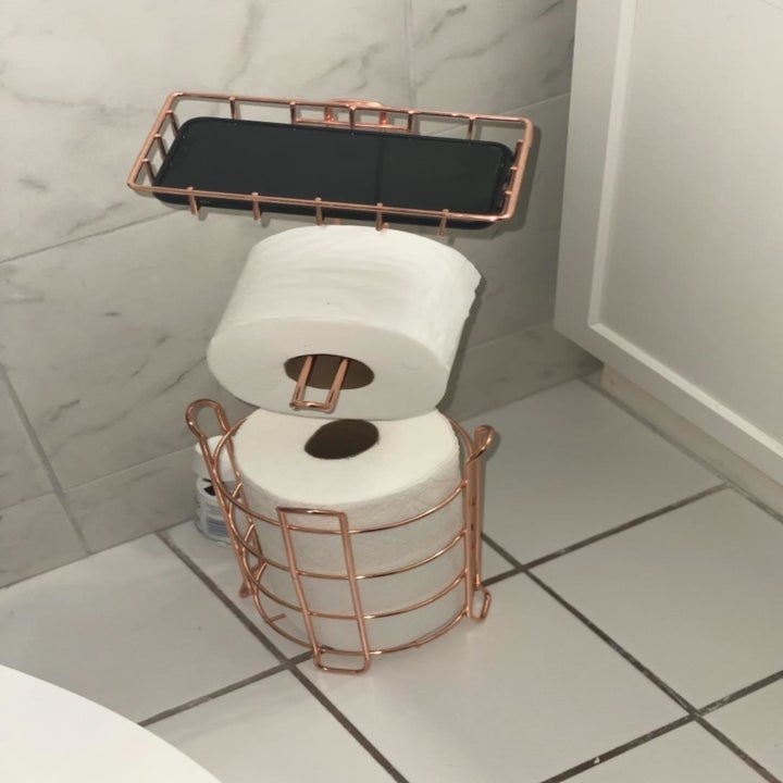 reviewer photo showing the toilet paper stand in their bathroom with phone on top in the holder