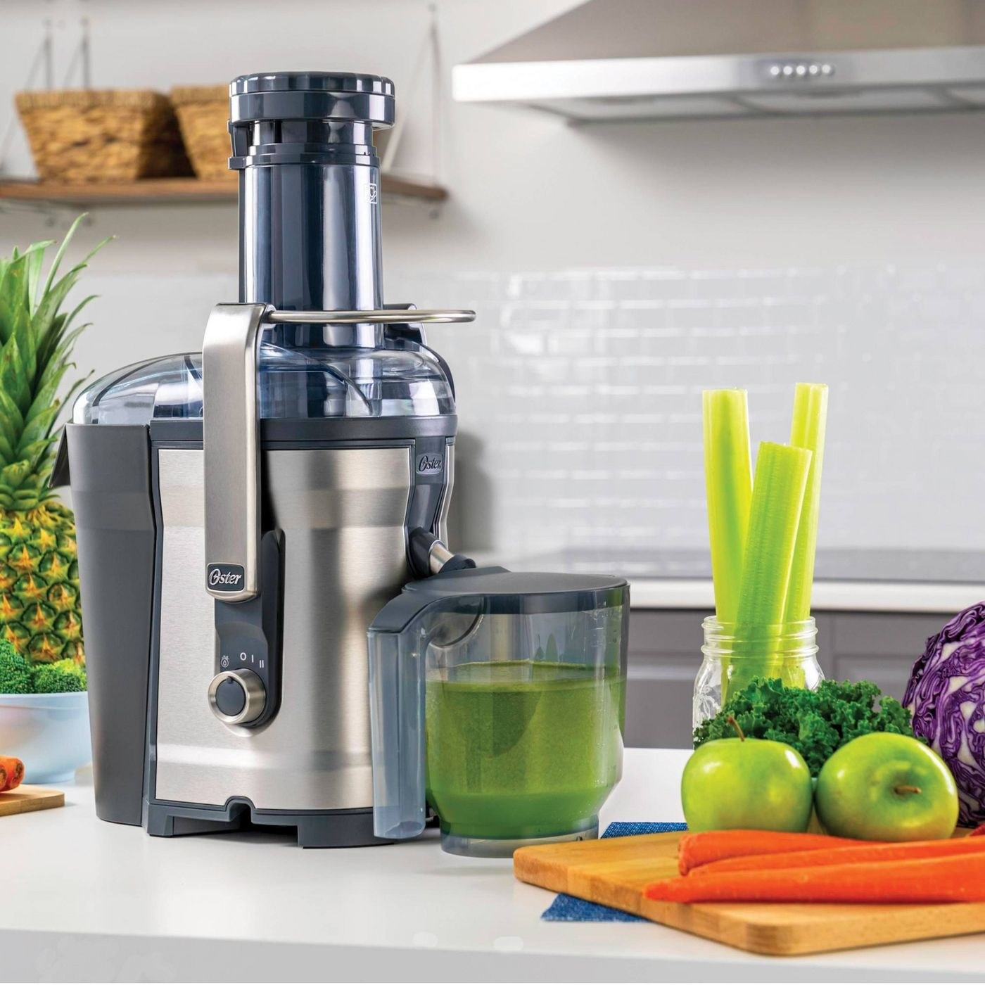 oster juicer catching green celery juice in a separate container