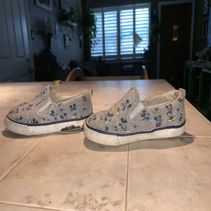 A pair of scuffed white soled shoes