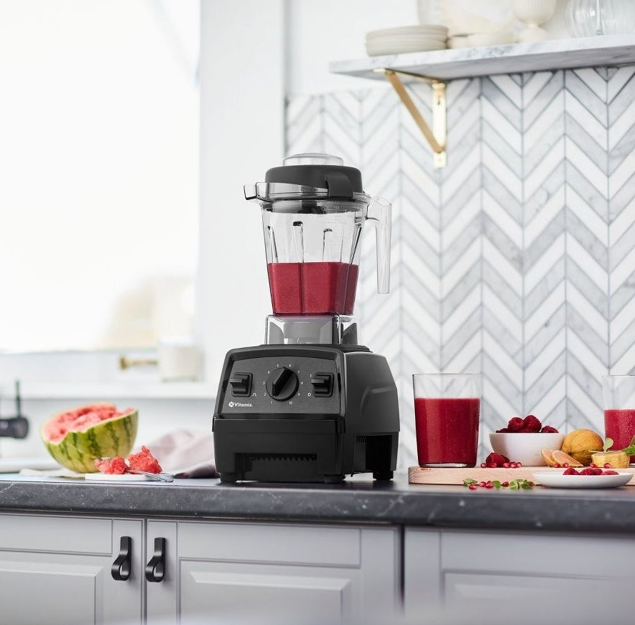 black vitamix blender with a fuchsia smoothie inside of it