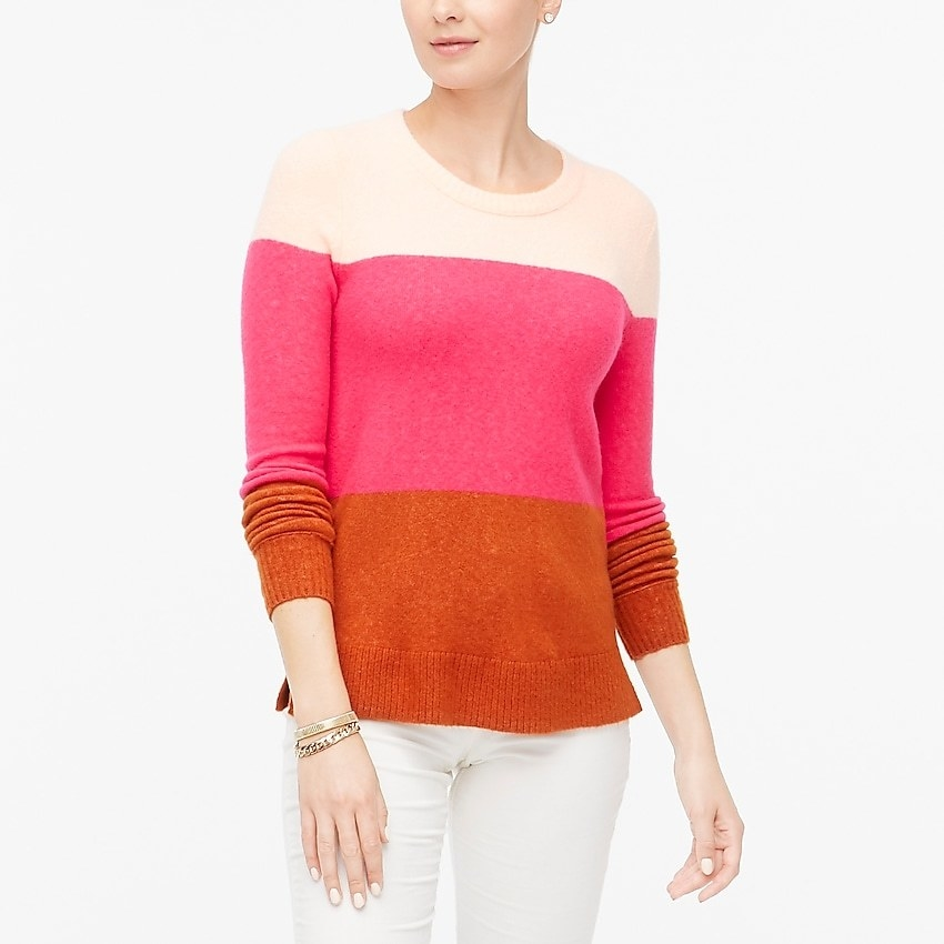 a model in a color blocked sweater with off white, pink and orange sections