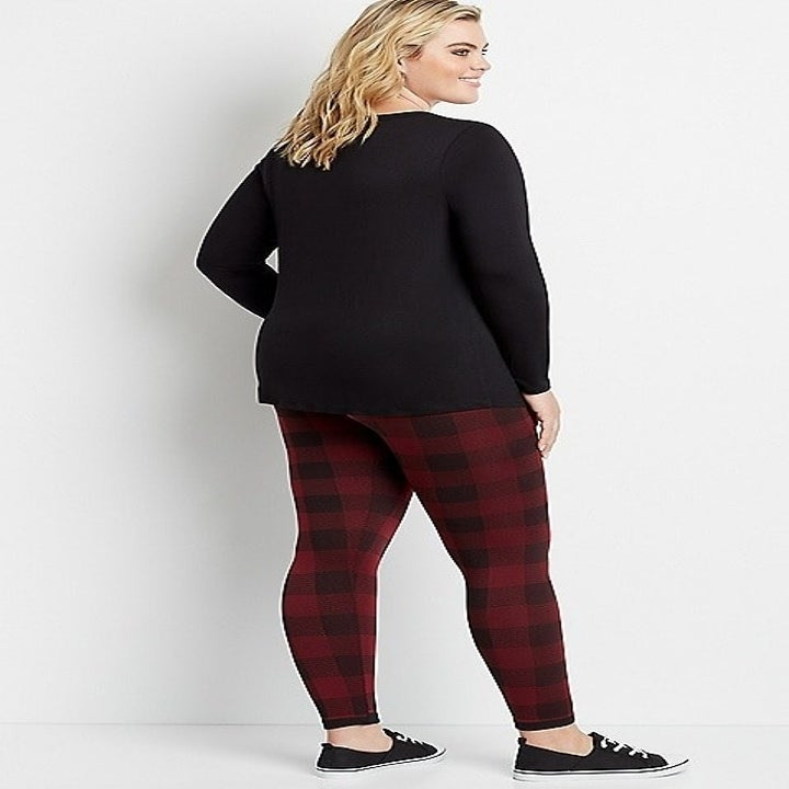 a model in buffalo check red and black leggings turn to show the back