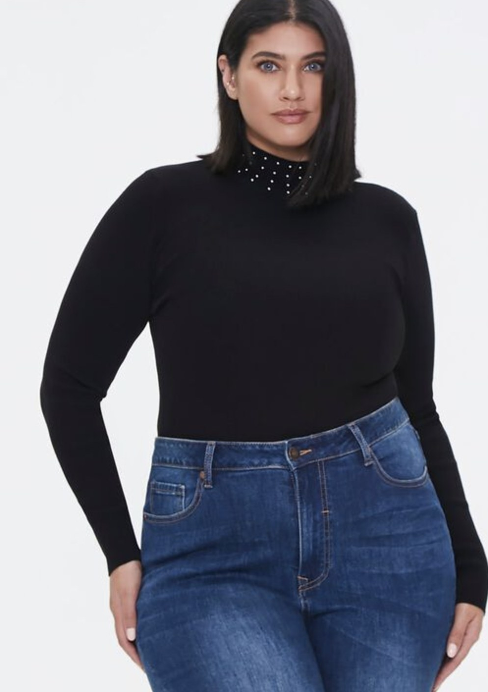 Model is wearing a black mock neck top with studded neckline and blue jeans