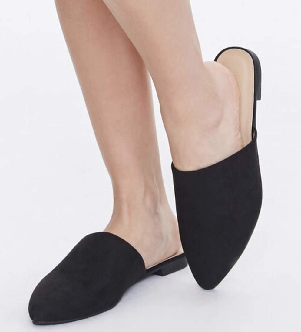 Model is wearing black pointed mules