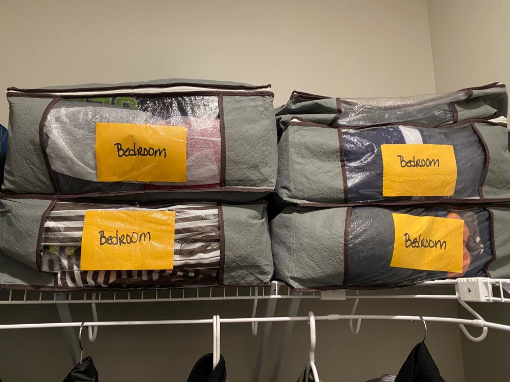 reviewer photo showing foldable storage bags filled with clothing and labeled on top shelf of their closet