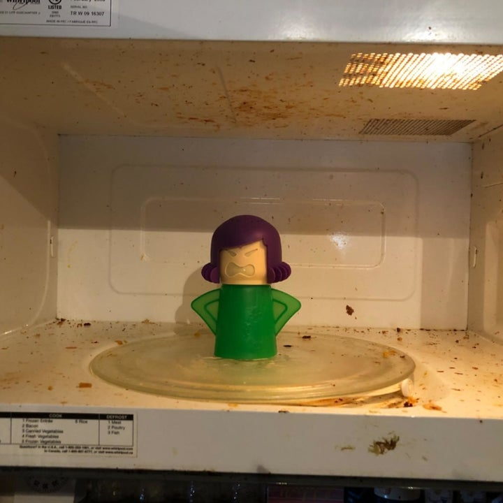 A reviewer's before photo which shows their dirty microwave and the cleaner sitting inside