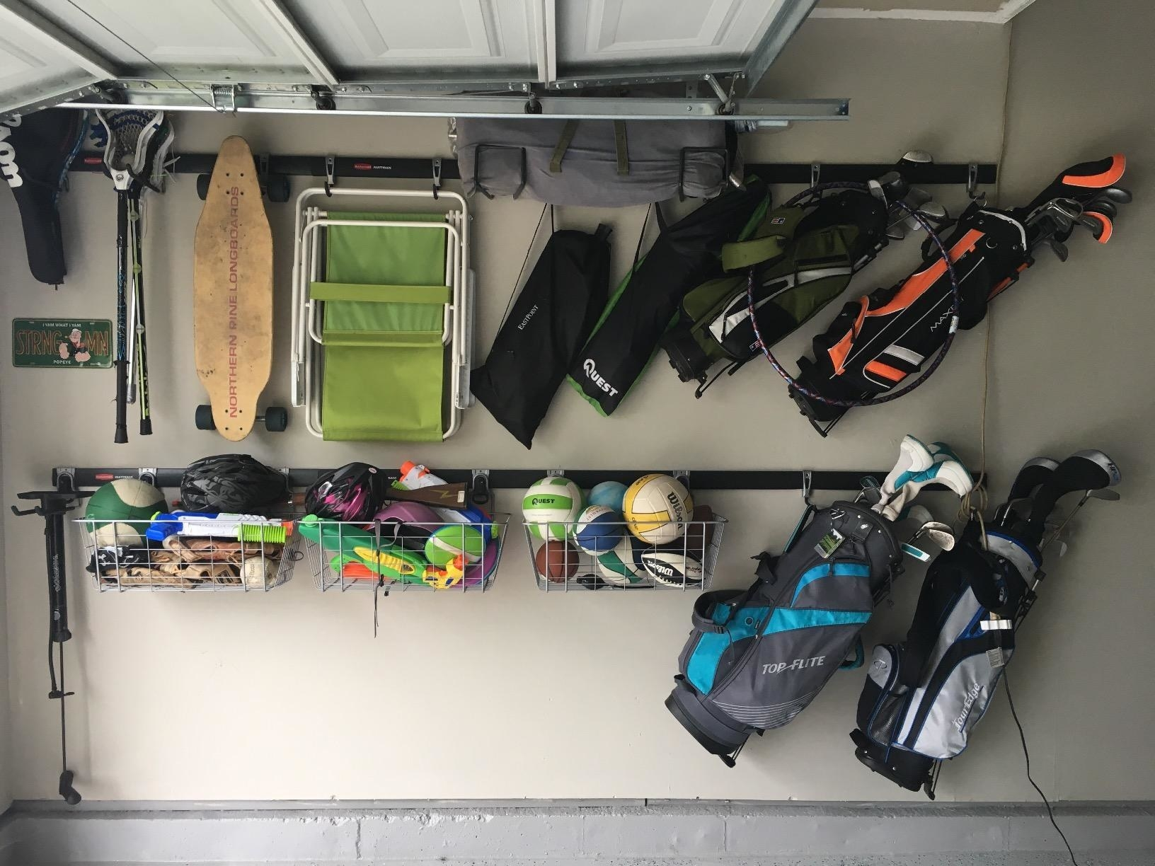 reviewer photo showing their garage completely organized with everything on their wall hanging from the track rails, including beach chairs, golf clubs, kids' toys, etc.