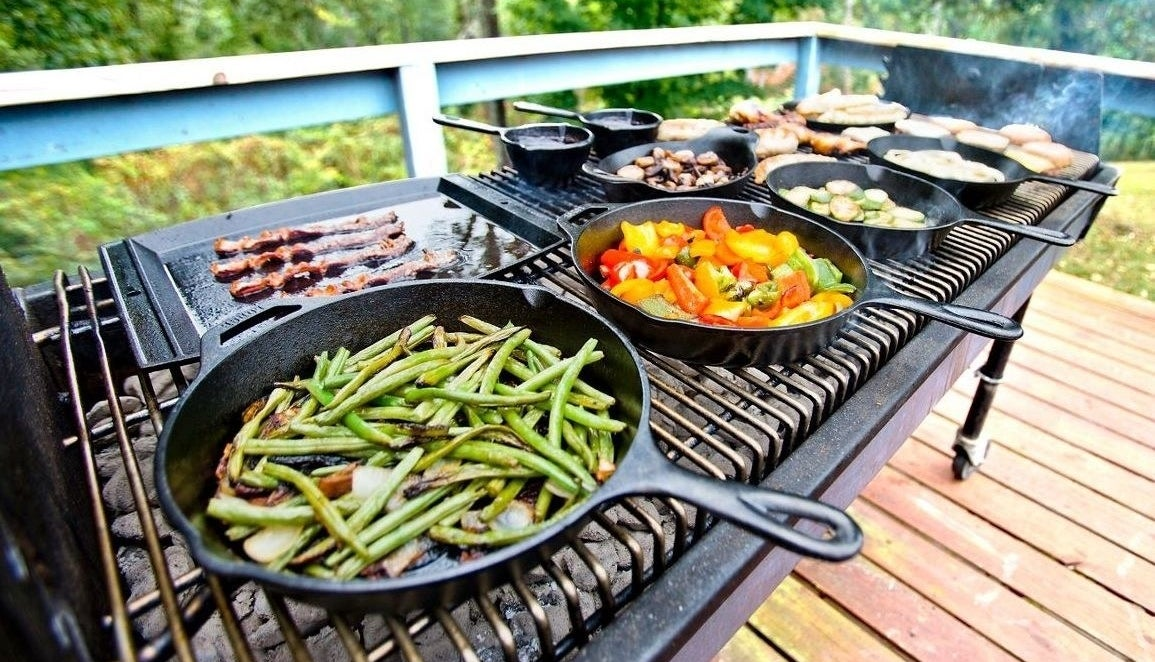 multiple cast iron skillet on an outdoor grill cooking vegetables