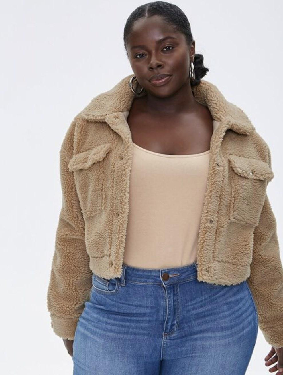 Model is wearing a tan sherpa jacket, beige tank top and blue jeans
