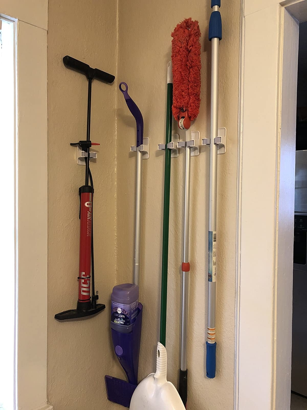 reviewer photo showing the individual clips arranged on a wall to hold a brom, Swiffer, duster and tire pump