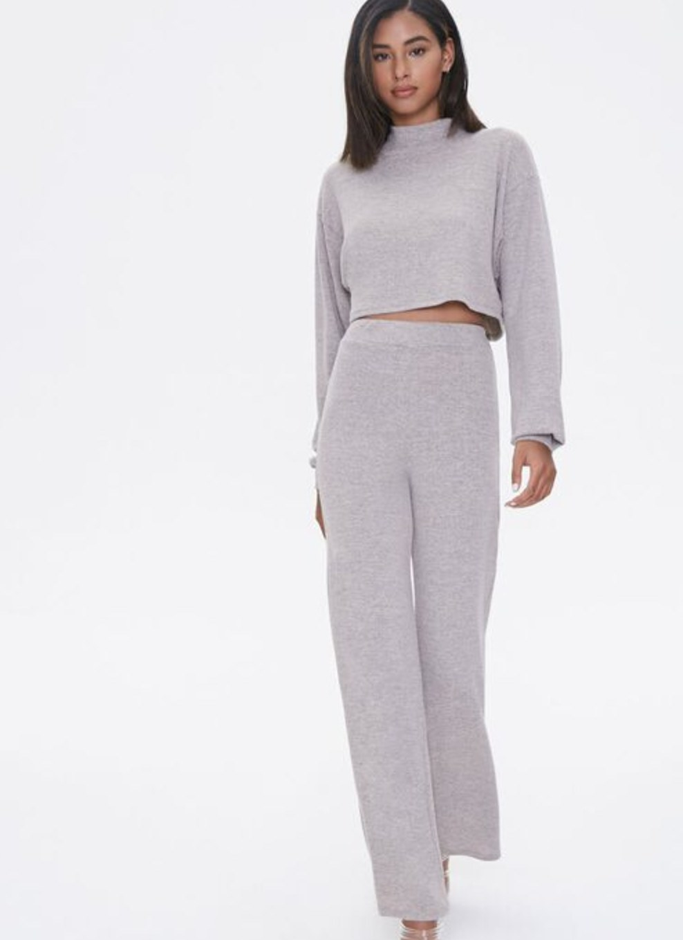 Model is wearing a grey mock neck sweater and matching pants