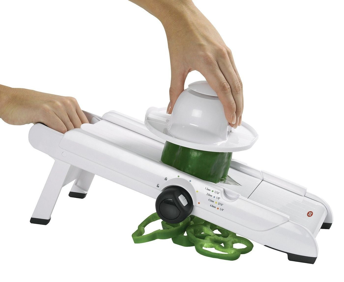 person using mandoline slicer to create thin, even slices of green pepper
