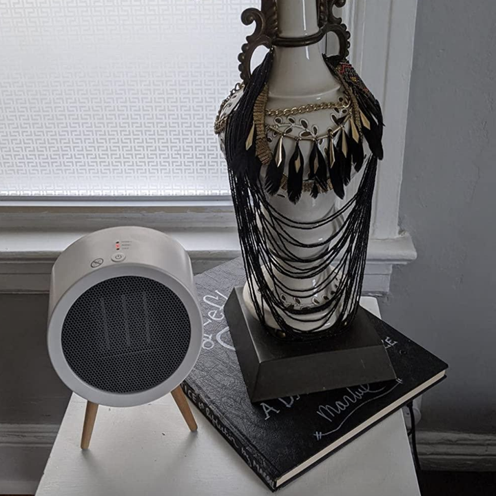 reviewer photo of the space heater on nightstand