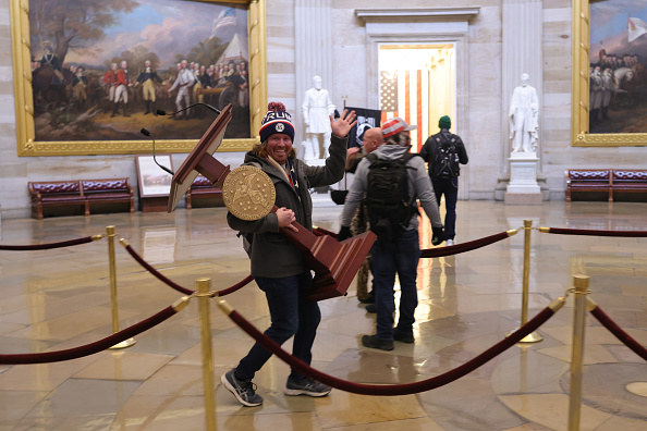 A rioter smiles at a camera while walking off with a podium from the Capitol