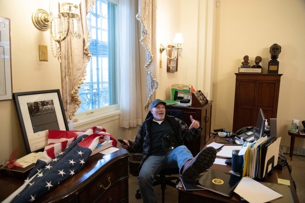 A rioter sitting in a chair at a desk in Nancy Pelosi's office