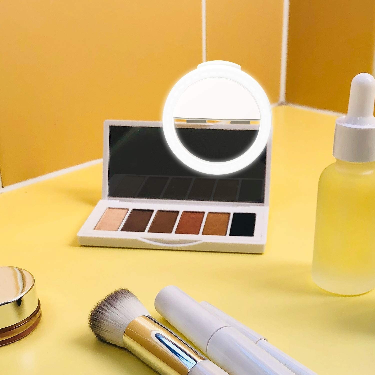 makeup palette with circular ring light clipped on