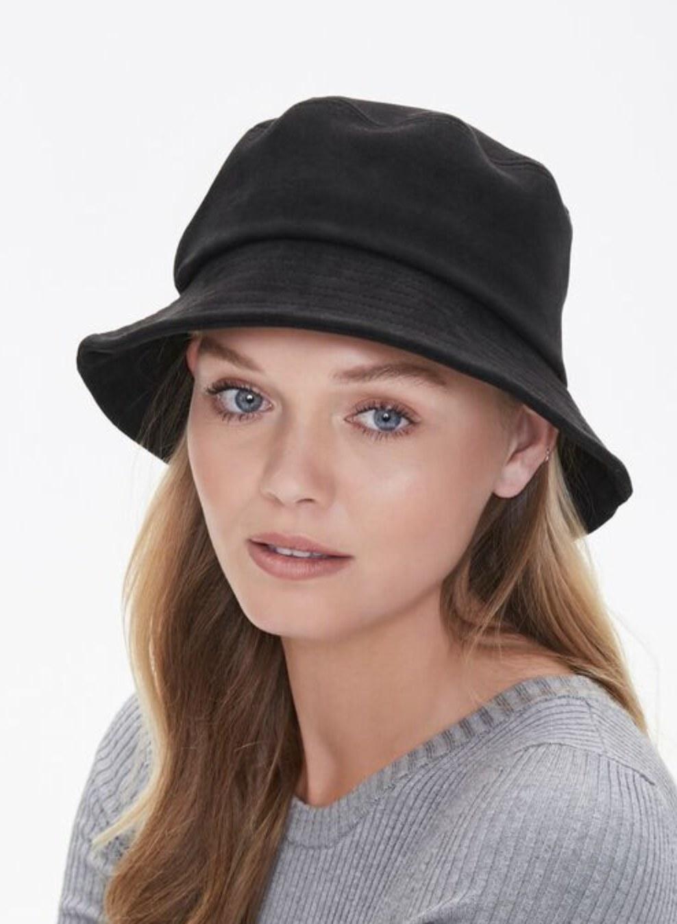 Model is wearing a black bucket hat