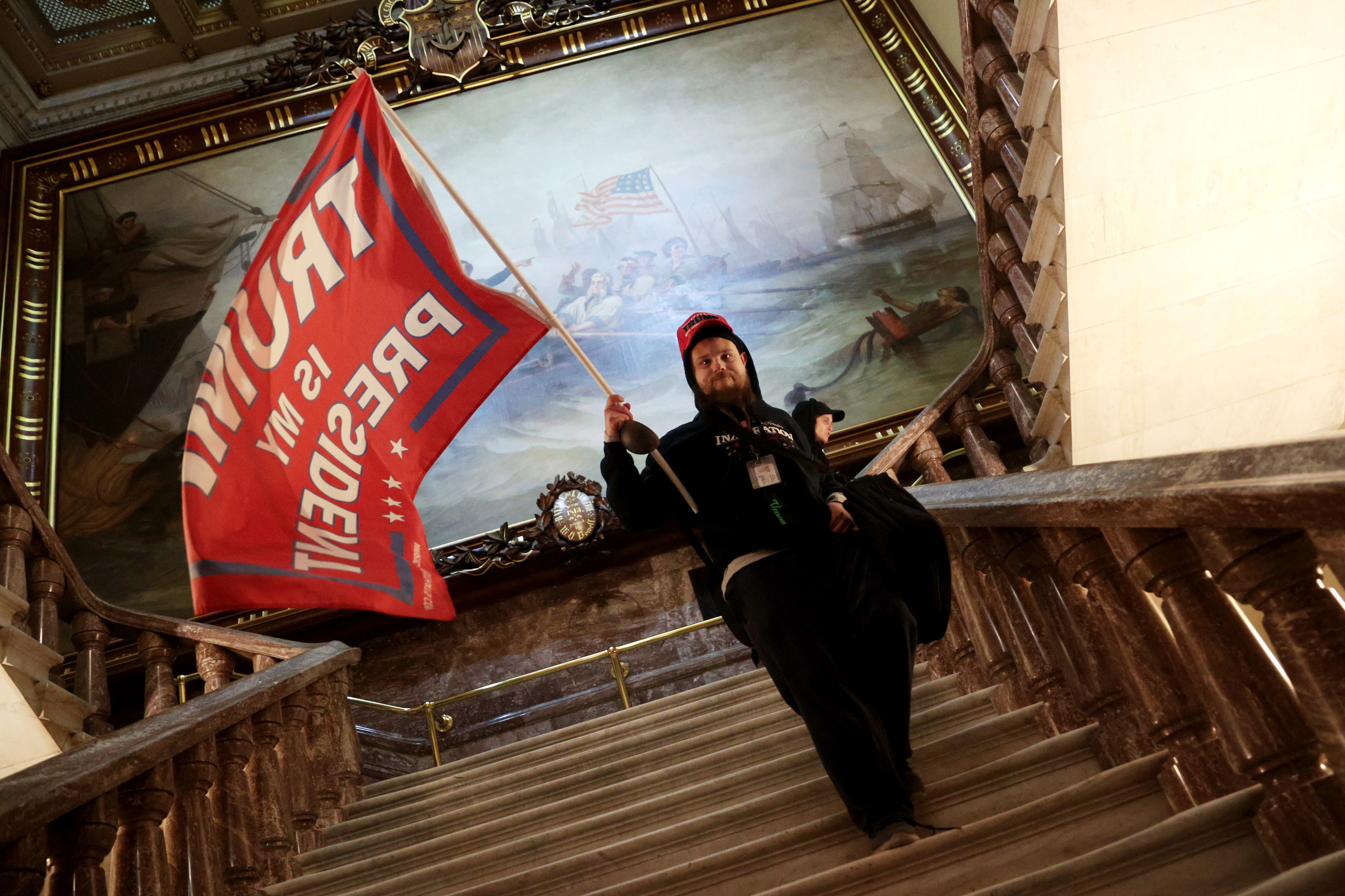 "A man descends a staircase waving a red flag that says ""Trump is my president"""