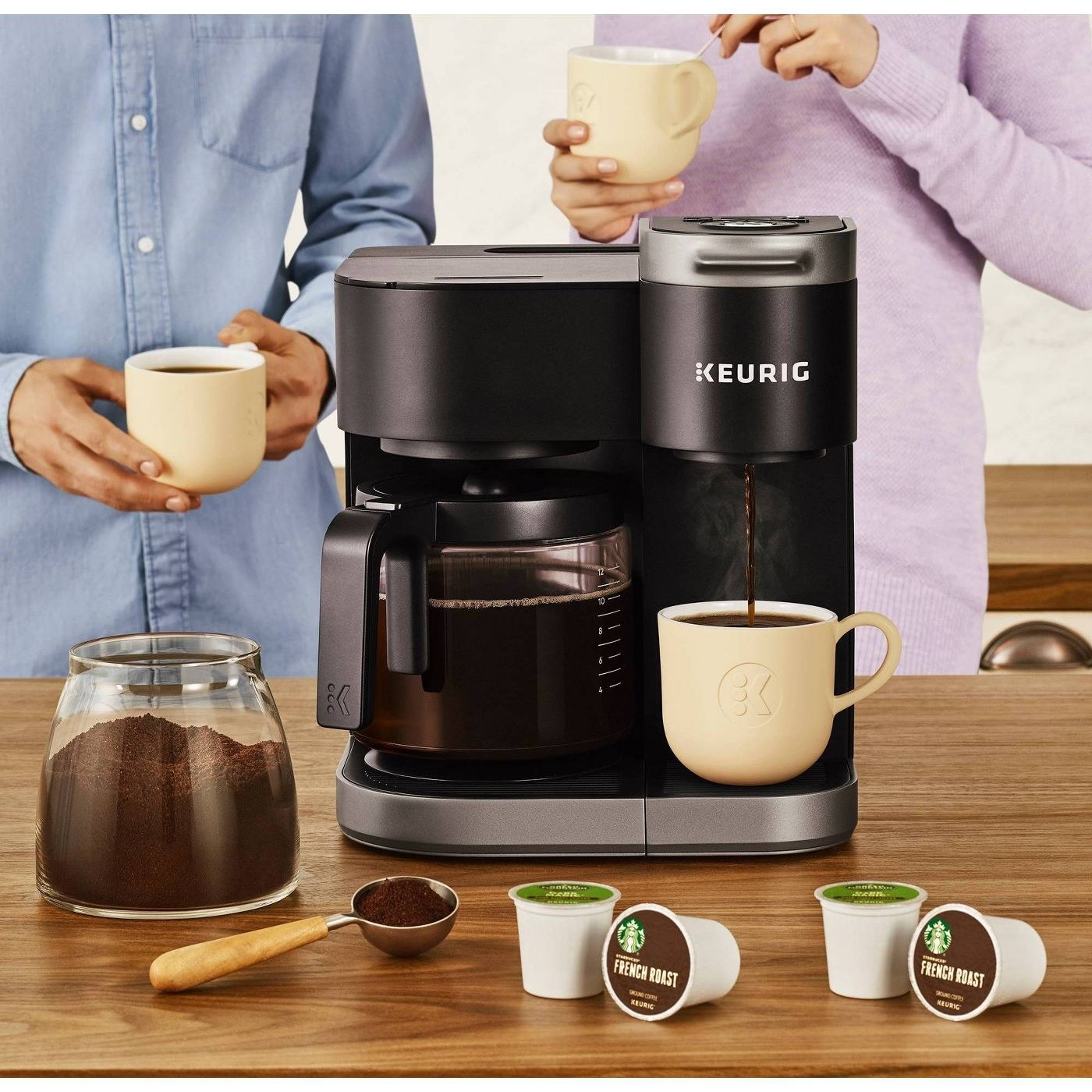 keurig machine with a full coffee pot on the left and one mug on with coffee pouring in on the right