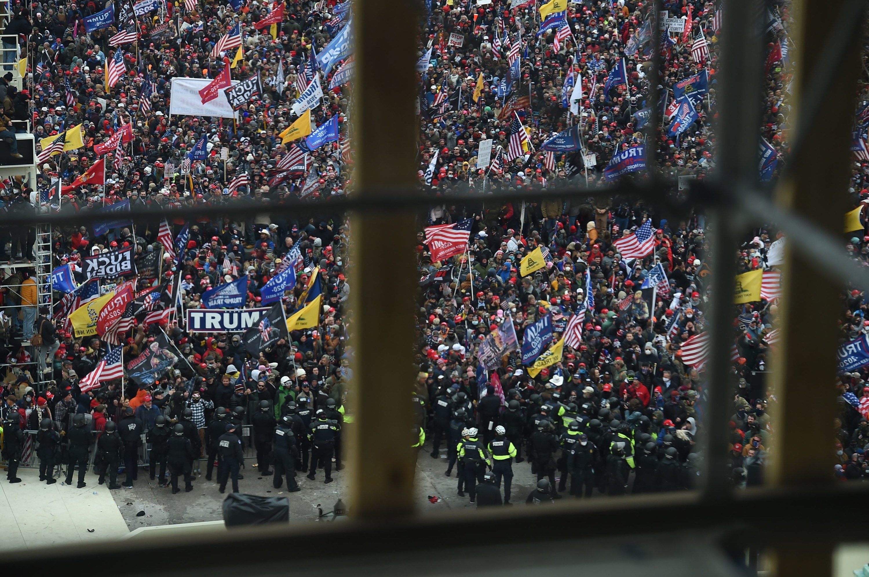 "A large crowd of Trump supporters, waving US flags and flags that say ""Trump 2020"" and ""don't tread on me"" stand behind a line of police officers, as seen through out-of-focus scaffolding in the foreground"