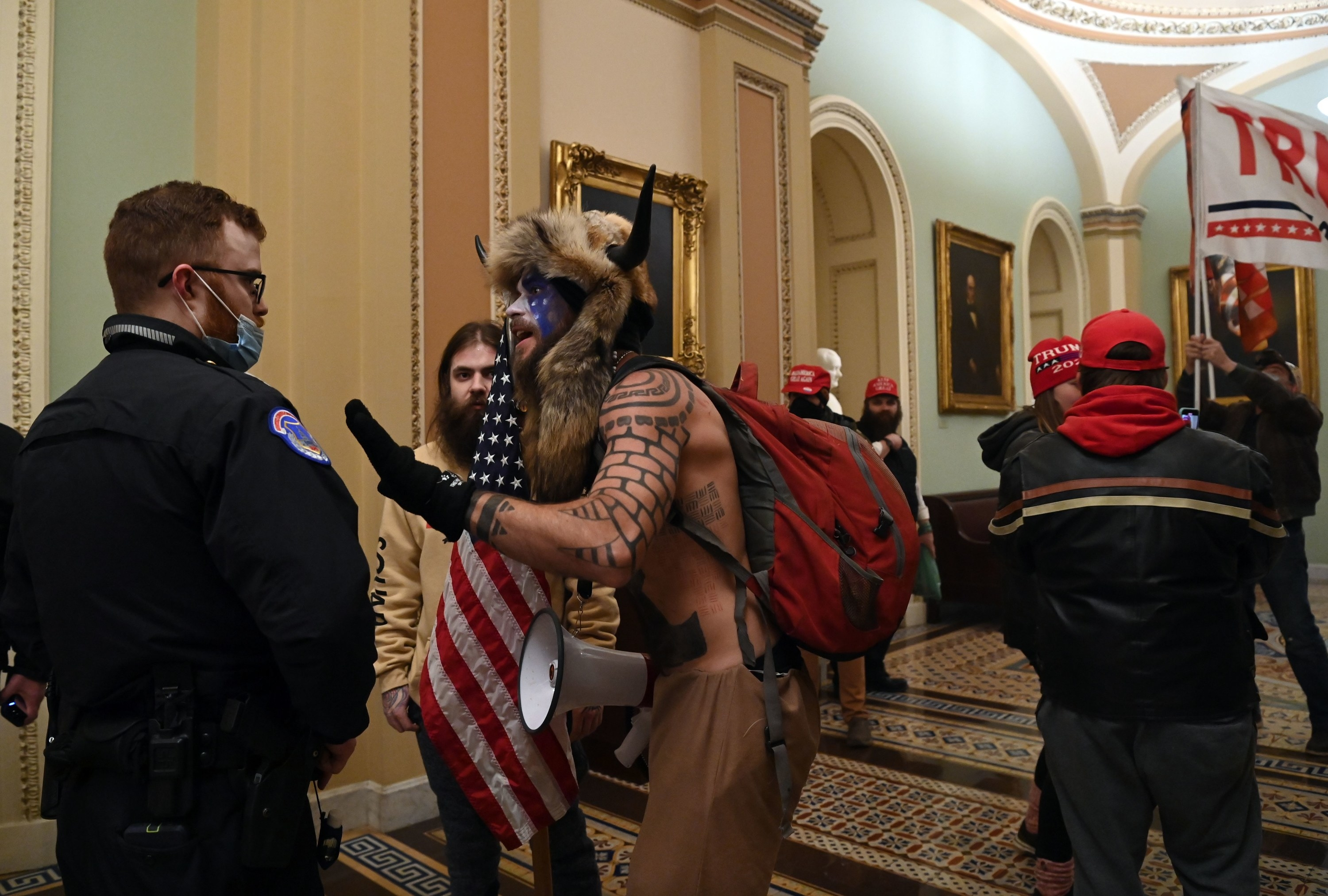 Police officers talk to Trump supporters, including a shirtless man with a backpack who wears face paint and an animal hide with horns over his head
