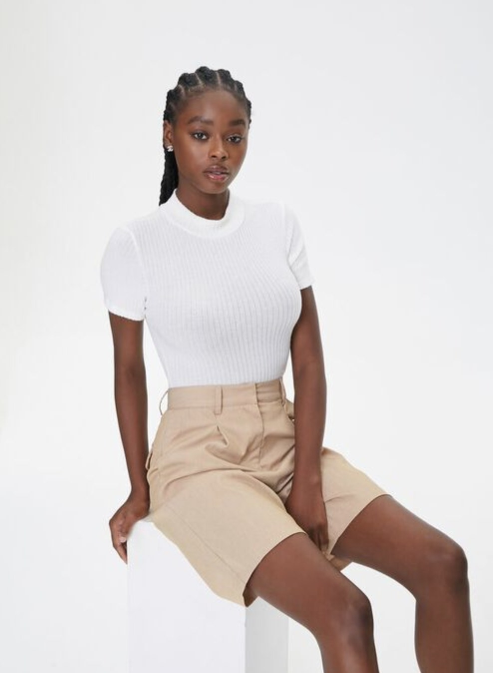 Model is wearing a white top and beige shorts