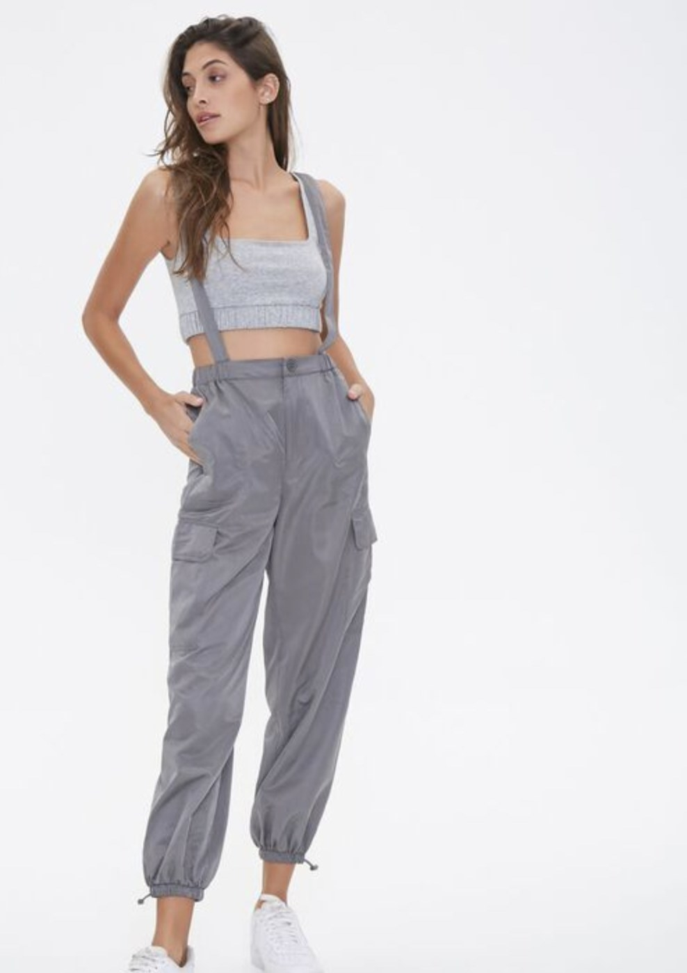 Model is wearing grey overall joggers and a top