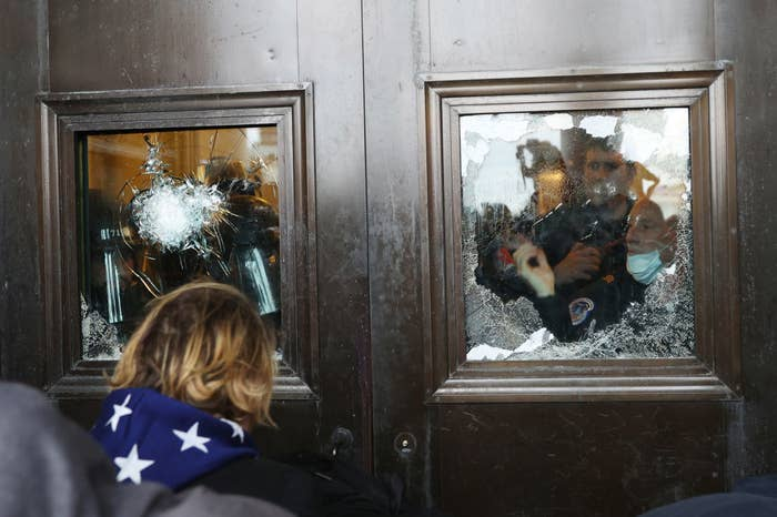 Rioters and police on opposite sides of Capitol entrance doors with the windows cracked