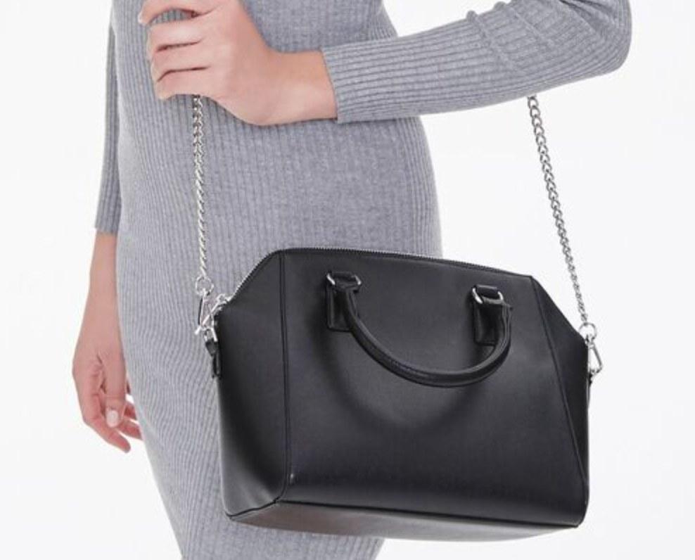 Model is holding a black satchel purse