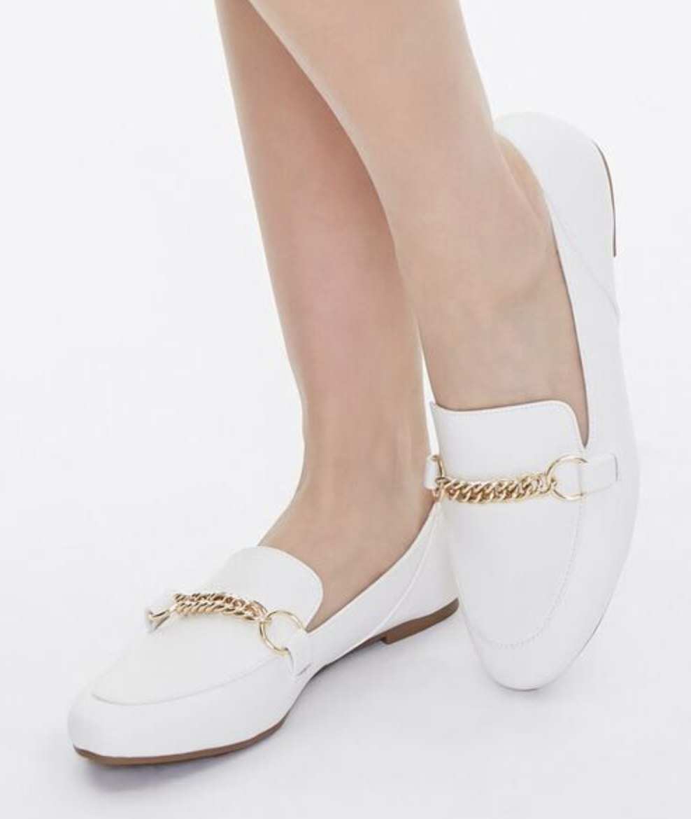 Model is wearing white leather loafers
