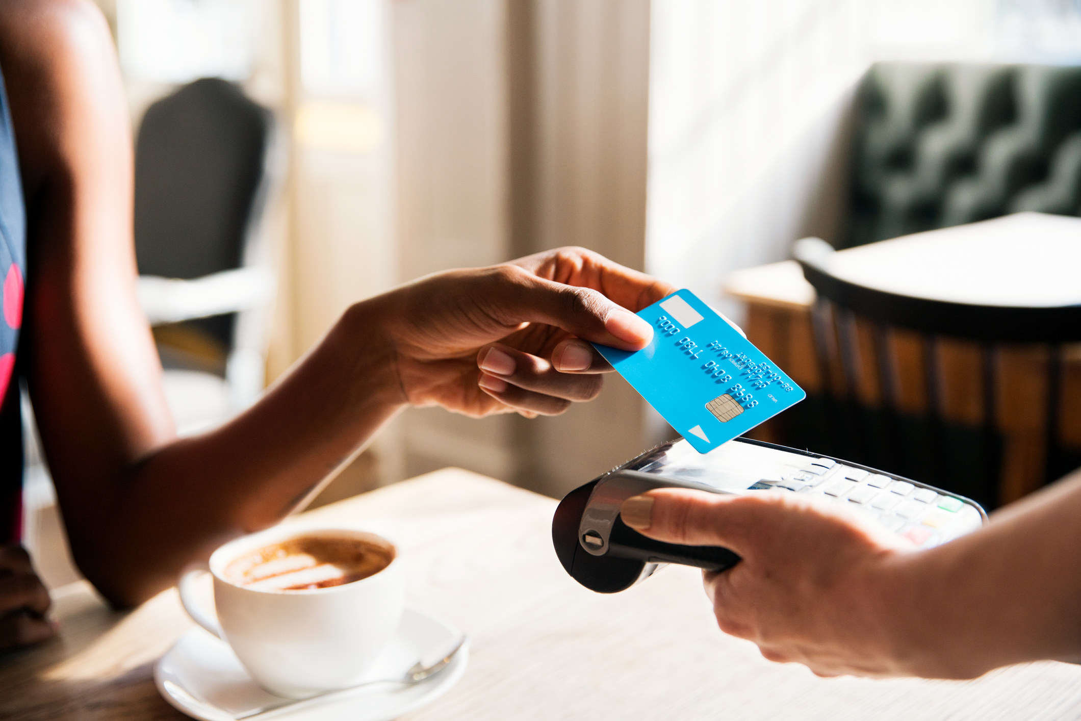 Model using a credit card to purchase coffee