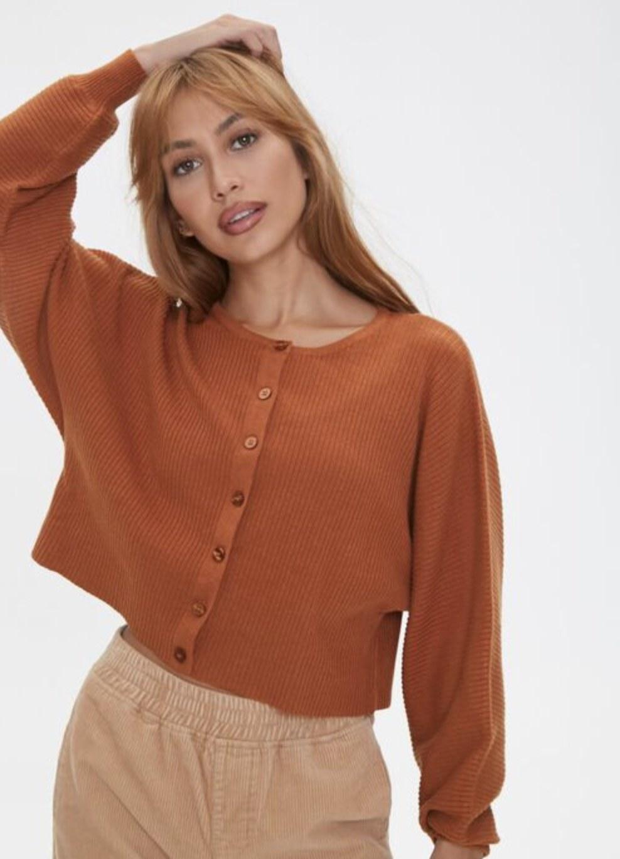 Model is wearing a burnt orange cardigan and tan pants