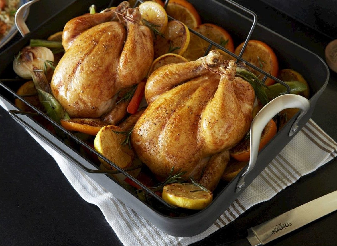 two chickens roasting on a rack in a roasting pan with vegetables underneath