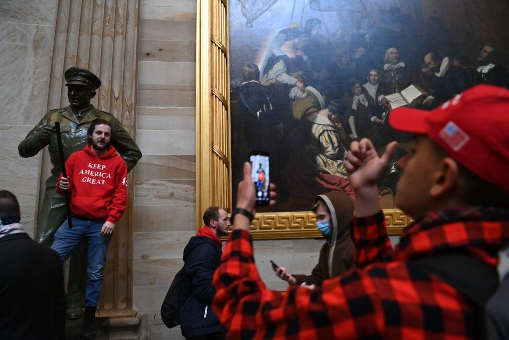 Man taking a photo of a fellow rioter who is posing next to a statue in the Capitol
